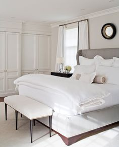 McGill Design Group!    white & gray chic bedroom design with gray linen wingback headboard bed, small black & gold convex mirror, gray walls paint color, chic white bench with slim legs, soft pink ruffled bolster pillow, black nightstand and built-ins cabinets closets.