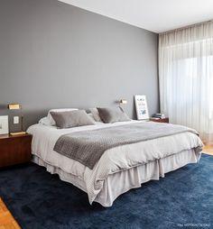 Quarto de casal tem parede pintada de cinza, roupa de cama nos mesmos tons e tapete azul.