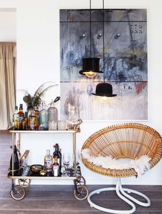 Lovely little Corner -  hats as hanging lamps add a lyrical light mood to a cozy seating area with bar car, round rattan chair with with white fur throw, and abstract painting. Casinha colorida: Uma casa eclética e familiar na Escandinávia