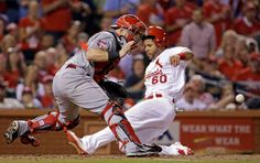 Beating the throw -  Cincinnati Reds catcher Tucker Barnhart, left, waits for the throw as St. Louis Cardinals' Tommy Pham scores on a double by Matt Holliday during the third inning of a baseball game on Sept. 23 in St. Louis. -  © Jeff Roberson/AP Photo