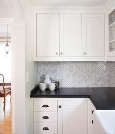 gray cabinets; black counters; slate herringbone floor; marble hex