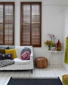 stores vénitiens en bois foncé, canapé blanc dans le salon, coussins de salon colorés