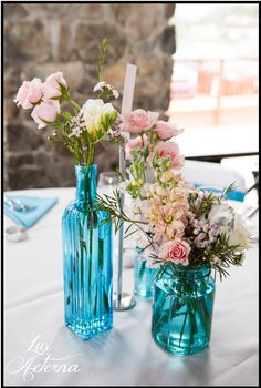Blue bud vase centerpieces with blush flowers