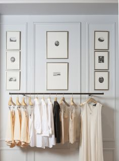 Camisoles and blouses hang below a gallery wall. Read about our #CM5thAve flagship store's decor from @One Kings Lane https://www.onekingslane.com/live-love-home/club-monaco-decorating-ideas/