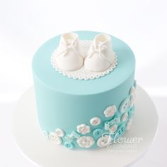 Baby shower button cake topped with a cute pair of booties. All items made out of sugar.