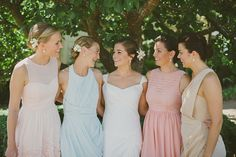 These bridesmaids chose their own gowns in different pastel hues, but their hairstyles and flowers gave the party one cohesive look.