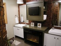 Having a fireplace in the bathroom isn't too uncommon, but what about having one built right into a custom vanity below a flat-screen television? Matt Muenster was able to add plenty of wish-list gadgets to this tiny master bathroom, including a modern fireplace, a television and a body dryer. Another feature that sets this small space apart is its unique wood-tiled walls, a decor element that immediately adds visual warmth. #diynetwork