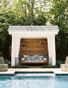 Chic pool cabana features plank walls lined with a wood daybed dressed in white and blue pillows illuminated by three chandeliers and finished with white and blue outdoor curtains.