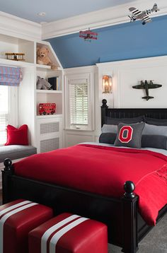 Fun red blue gray boy's bedroom design with black wood poster bed, striped red & white leather ottomans, red & gray flannel bedding, striped blue & pink roman shade, built-in window seat, gray flannel cushion, red pillow, airplanes and crown molding. white red blue gray boy's room colors.