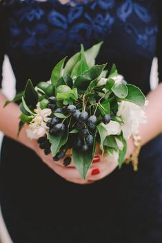 Green, white and navy bridesmaids bouquet with greens and blue berries wrapped in navy ribbon