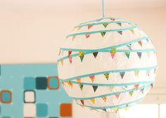 A tutorial with photos and instructions on how to decorate a paper lantern with miniature fabric bunting. Make over your rice paper lantern today!