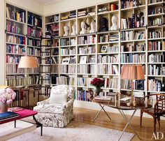 Adjustable picture lights by Ann-Morris are mounted on the room's bookshelves, and the busts are from Galerie du Passage