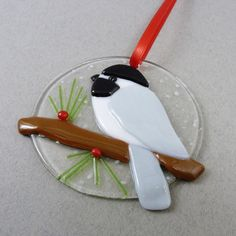 Invite nature indoors by dressing your windows with a bit of winter cheer! This fused glass chickadee window ornament will add a little life and character to your windows during the cold winter months.    This handmade bird suncatcher makes the perfect Christmas gift for the bird lover on your list.