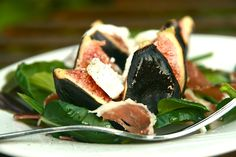 Fig and goat's cheese on a bed of new greens with slices of prosciutto.