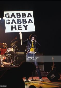 Ramones singer Joey Ramone holding a sign reading 'GABBA, GABBA, HEY' while performing in New York, 1978. Drummer Tommy Ramone is in the background.