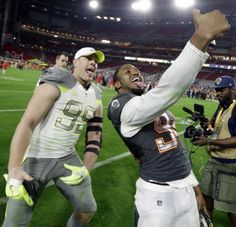 Houston Texans' J.J. Watt (99) poses for a selfie with St. Louis Rams' Robert Quinn after Team Irvin defeated Team Carter 32-28 in the NFL Football Pro Bowl Sunday, Jan. 25, 2015, in Glendale, Ariz. (AP Photo/Mark Humphrey)