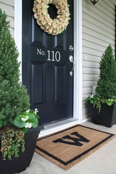 Fauxx pine trees flank black front door with wreath of roses