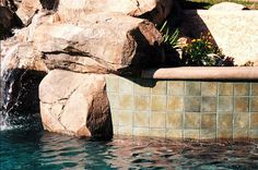 Natural Pool Design by Classic Pool & Patio featuring rocks and waterfall.