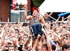 Publicul de la un festival de muzică din Melbourne, Australia, ține cu mâinile un băiat într-un scaun cu rotile pentru a vedea spectacolul.