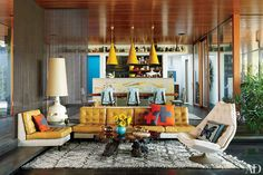In the living room of Jonathan Adler and Simon Doonan's vacation home on Shelter Island, mod furniture and a shaggy, vintage Beni Ourain rug create a groovy-chic vibe