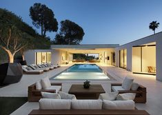 lounge chairs and a zero edge pool surrounded by pocket doors | Modern backyard at Hillcrest in Beverly Hills by Boswell Construction #buildboswell
