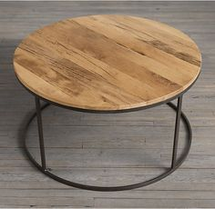 RH's Watts Reclaimed Oak Round Coffee Table:Our modern-minimalist table juxtaposes steely metal with the warmth of reclaimed wood. The tabletop is handcrafted of solid oak timbers salvaged from decades-old buildings in Russia; a silhouette ring base echoes the circular disc shape of the wood.