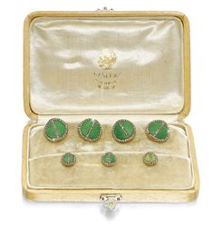 A FABERGÉ JEWELLED GOLD AND ENAMEL DRESSING SET, WORKMASTER AUGUST HOLLMING, ST PETERSBURG, 1899-1904 comprising: a pair of cufflinks and three studs, all formed as discs with canted surfaces enamelled in translucent green over hatched engine-turning, divided by and bordered with rose-cut diamonds, struck with workmaster's initials, 56 standard, scratched inventory numbers 64913 (cufflinks) and 64914 (studs), in original Fabergé fitted wood case Estimate 8,000 — 12,000 GBP  LOT SOLD. 61,250…