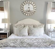 Upholstered Headboard with Nailhead trim, Barbara Barry Bedding, Sunburst Mirror, and light grey walls - perfection