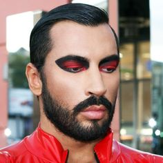 I choose this image because of the eye makeup. I like that the red and black makeup goes with his shirt. I also think it makes him look superior.