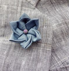 An ice blue silk lapel pin flower boutonniere for elegant men and women, made in the Japanese tsumami kanzashi style! I used a blue dupioni silk to make the flower, added a rainbow druzy quartz bead to the center, and mounted it on a tie tack with butterfly clutch back. Complements a suit, blazer, vest, hat, cardigan, or sports jacket. Kanzashi flowers are made from folded fabric squares, one petal at a time. Originally, apprentice geisha made kanzashi hair accessories from their old…