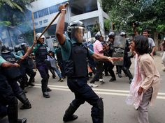 A police officer uses his baton against an activist during a protest against the government in Dhaka, Bangladesh. Demonstrators demanded that the government withdraw a power-tariff hike marched toward the energy ministry.