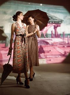 Two models in print dresses standing in front of a background painted by Eugene Berman, 1947. #vintage #fashion #1940s