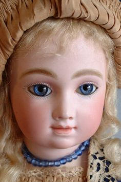 "This stunningly beautiful 22"" André Thuillier Bebe is the stuff that very sweet dreams are made of. With a perfect, fully marked bisque head, deep blue paperweight eyes, a closed mouth, classic soft features, pierced ears and her original blond mohair wig-she will delight you.  A11T"