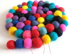 5) And continue sewing the balls together (in this photo, red to pink, pink to dusty blue, dusty blue to blue, blue to black and so on). This is a bit tricky at first; try to keep the circle shape while sewing, and try not to make gaps between the balls!
