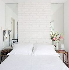 By placing long vertical mirrors on both sides of the bed, this Brazilian room from Casa e Jardim spotted on Stylist creates an optical illusion, giving the impression that the room continues beyond the bed. Try this trick by placing mirrors on the far end of a tiny room, so the reflective surface will bounce light around the room.