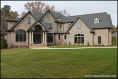 European home exteriors feature complex rooflines, stucco, brick and stone facing, and intricate window detailing.  In this photo, a version of the Avonstone Manor floor plan by Garrell Associates incorporates medieval design with modern color schemes and details.