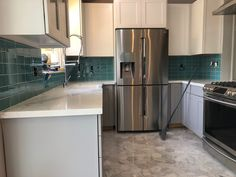 Gorgeous backsplash using Sage Green Glass Subway Tile, it is the perfect pop of color for this updated kitchen remodel.