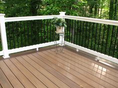 Longevity black aluminum balusters with white PVC #deck railing and WOLF PVC decking amberwood flooring.