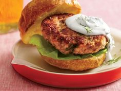Salmon Burgers. 2 cans (6 oz each) Wild Planet Wild Alaskan Pink Salmon, drained and flaked; 2 lg eggs, lightly beaten; 3/4 c fresh or dried whole wheat or panko bread crumbs; 1/4 c finely chopped red onion 4 Tbsp chopped fresh dill; 1 1/2 tsp fresh lime or lemon juice; 1/4 c reduced-fat sour cream; 4 whole wheat sandwich buns, split and toasted; 4 lettuce leaves.