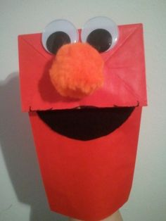 Elmo Paper Bag Puppet:  Paper bag  Wiggle Eyes  Orange pom pom nose  Black felt mouth, top lip outlined with marker!  Craft for kids to make at birthday party!