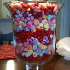 Valentines day table centerpiece.  I use a pillar candle in the middle then fill it up with candy AND around to hide it