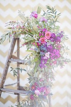 An old step ladder covered in flowers and eucalyptus leaves   Photo by Happy Confetti Photography
