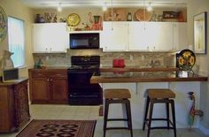 Our complete kitchen redo for under $4,000.  Looks unfinished slightly with the bottom cabinet a different color. Oops.
