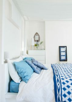 White walls, furniture and linen with splashes of bright blue textiles create a serene seaside bedroom.