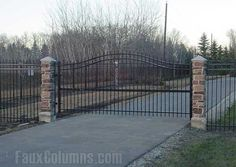 Wrought iron driveway gate flanked by two faux stone columns.