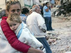 A woman holds a child as they stand in the street following the huge quake that…