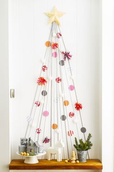 """Craft Your Own """"Christmas Tree"""" Use yarn to style a mini version on an empty wall or in a hallway. Enlist the kids to dress it to the nines with paper-circle """"ornaments"""" and felt, attached with tape."""