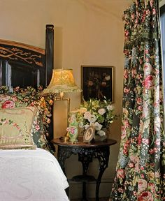 The black background of the pretty floral compliments the black bed. I love the fabric, but I would have used an ecru bedspread- I don't see white in the floral. Actually, rose or green would be even better. A pretty old fashioned look. www.lindafloyd.com