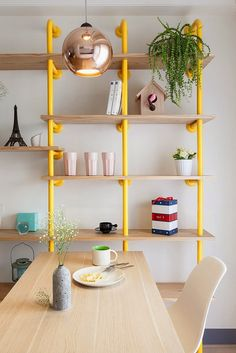 yellow tube bookshelf | Colorful modern apartment | Joyful Apartment by House Design Studio