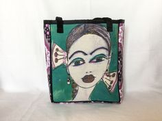 """Daphne - Telling in Teal This bag measures 13"""" wide by 15"""" high by 6"""" deep The image is painted and dyed on linen Daphne has on a pair of chunky faux pearl and purple bead earrings The back and sides are a beautiful purple patterned fabric The inside has a soft peach colored lining with a 5"""" x 7"""" open side pocket All seams are tailored with pretty black ribbon 10"""" black velvety straps"""